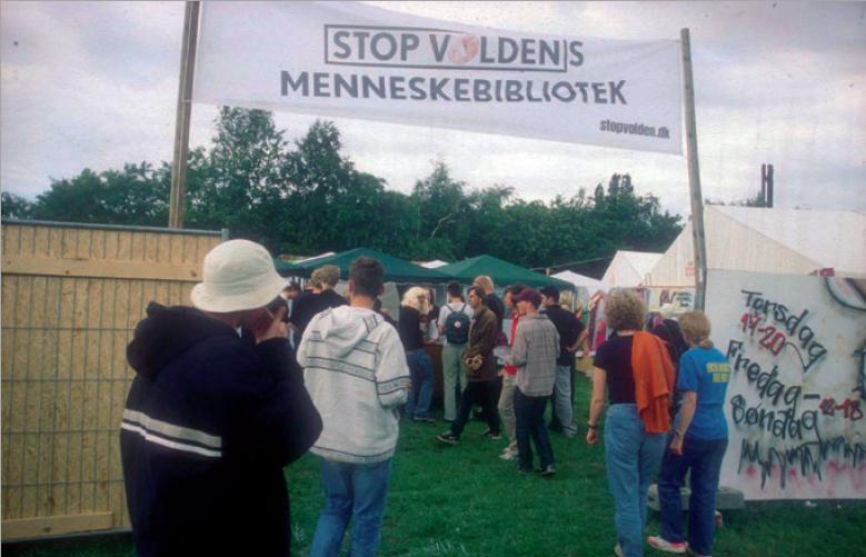Figure 3 – Entrée principale de la première           bibliothèque vivante, tenue lors du festival Roskilde en2000. La           bannière dit: Bibliothèque vivante «Stop à la violence».